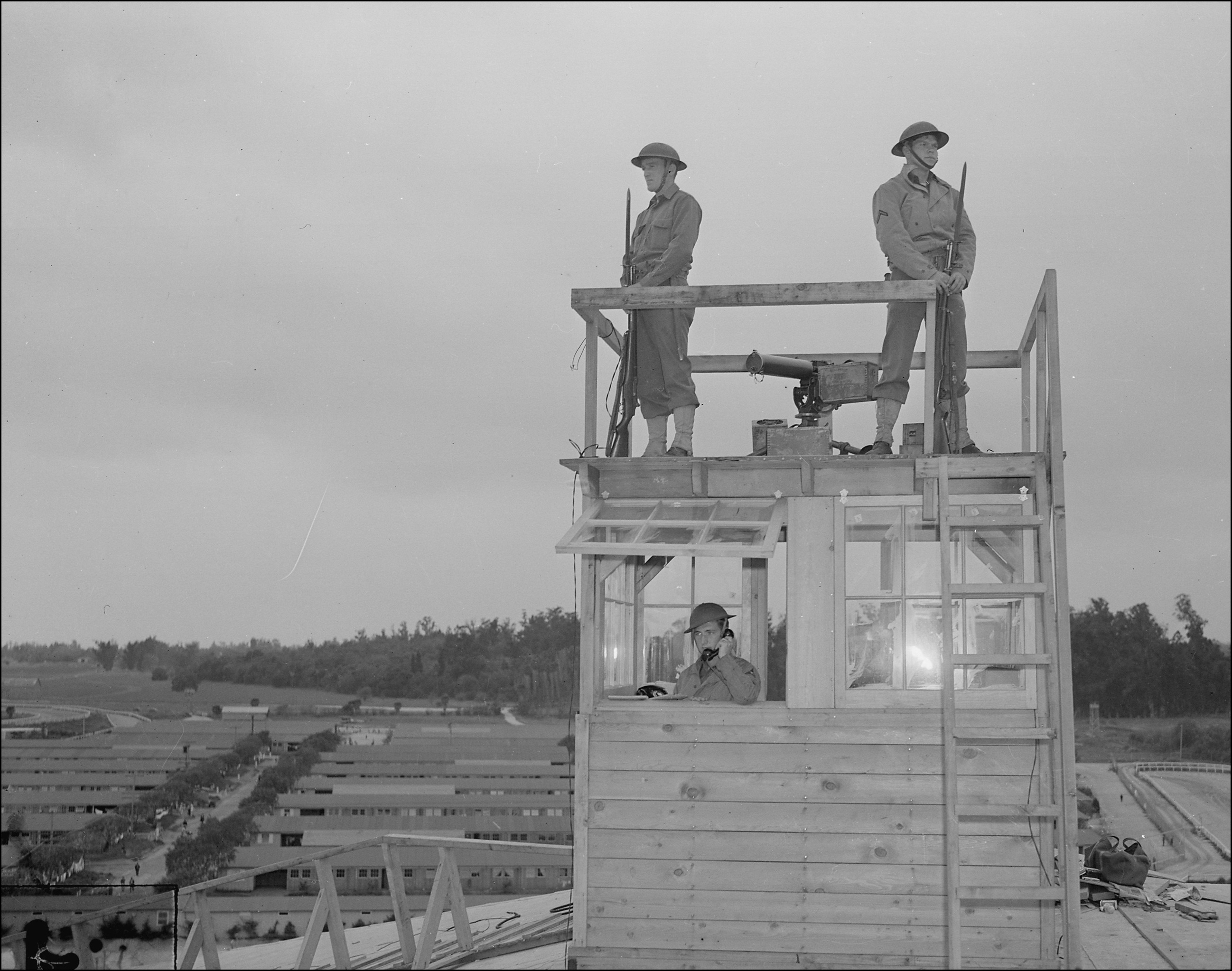 Arcadia, California. Military police on duty in watch-tower at Santa Anita Park assembly center, 1942, Courtesy of the National Archives and Records Administration